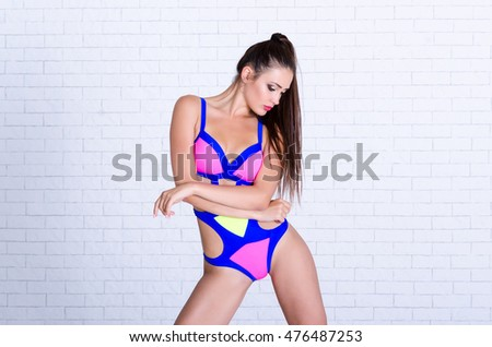 Young woman in colorful swimsuit. Photo over white brick wall.