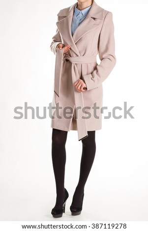 Young woman in conservative clothes. Neat cashmere coat and shirt. Female model in beige coat. Soft cashmere coat and shirt. - stock photo
