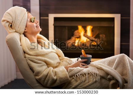 Young woman in cosy living room enjoying winter relaxation with face pack and tea, smiling. - stock photo