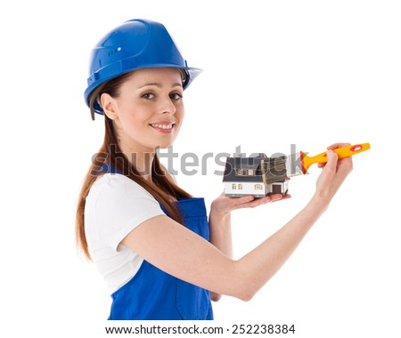 Young woman in  coverall with paintbrushes and model of house on a white background. Female construction worker. - stock photo