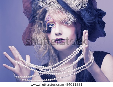 Young woman in creative doll-style with perl beads - stock photo