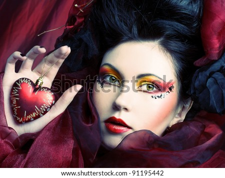Young woman in creative image with red heart in her hands.