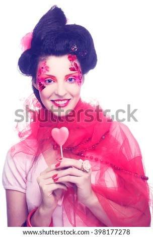 Young woman in creative image with sweet in her hands