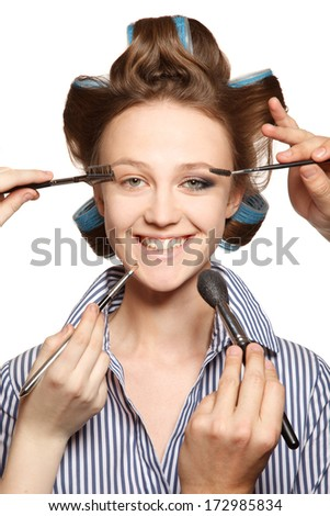 Young woman in curler in her hair and one eye with make-up,she is expressing her emotions.   With multiple hands applying make up. - stock photo