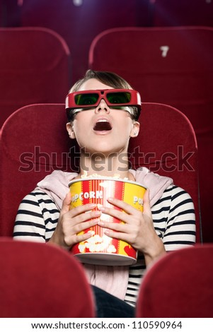Young woman in 3D glasses watching a movie - stock photo