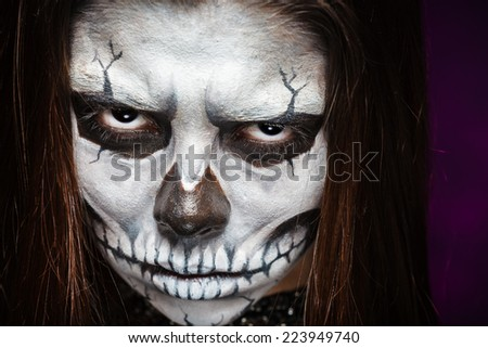 Young woman in day of the dead mask skull face art. Halloween face art. - stock photo