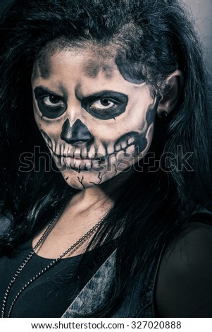 Young woman in day of the dead mask skull face art. Halloween face art - stock photo