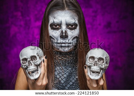 Young woman in day of the dead mask skull face art with two skulls in hands. Halloween face art.