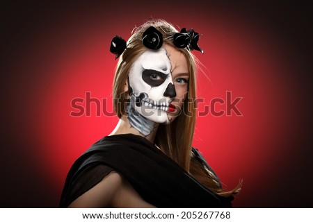 Young woman in dead mask skull face art. Halloween faceart over red background. Bodypainting. - stock photo