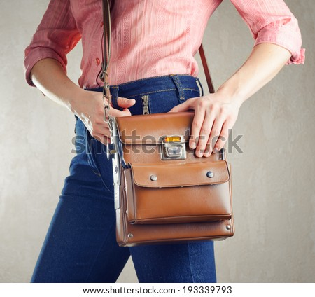 Young woman in deep blue jeans holding a bag. Retro style.