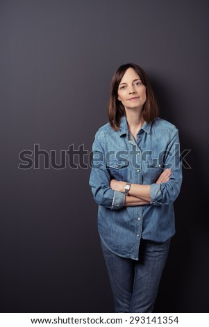 Young Woman in Denim Shirt and Jeans, Leaning Against Gray Wall Background with Arms Crossed and Looking at the Camera. - stock photo