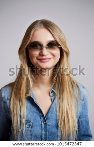 Young woman in denim shirt and shades, smiling