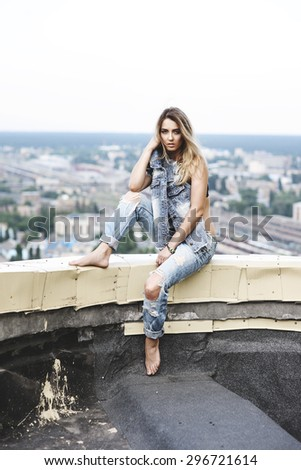 Young woman in denim sitting on the roof