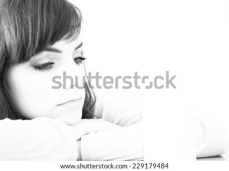 Young woman in depression laying her head on her arms thinking of something sad - stock photo