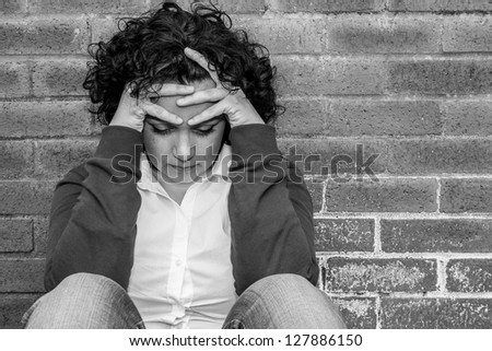 Young Woman in Despair sitting against wall - stock photo