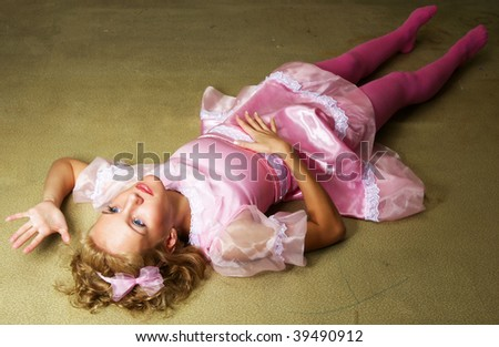 young woman in dolls dress laying on floor - stock photo
