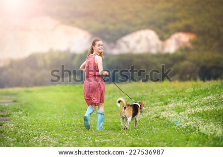Young woman in dress and blue wellies walk her beagle dog in green nature