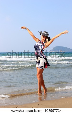 Young woman in dress and straw hat walking on beach - stock photo