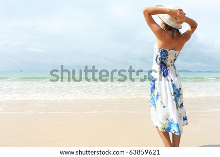 Young woman in dress holding a straw hat and looking to a blue sky - stock photo