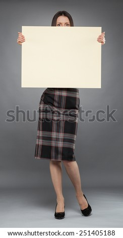Young woman in dress  holding blank placard , full length portrait on gray background - stock photo