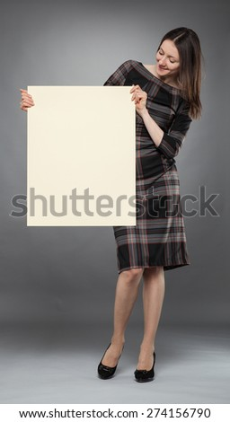 Young woman in dress  holding blank placard showing at it, full length portrait on gray background - stock photo