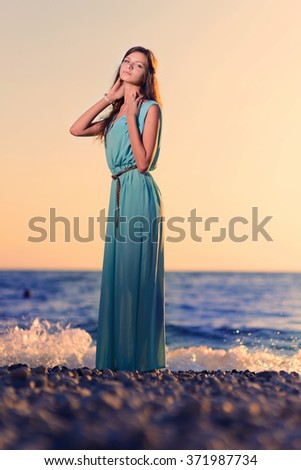 Young woman in dress on the beach at sunset against the sun. Feeling free and joyful