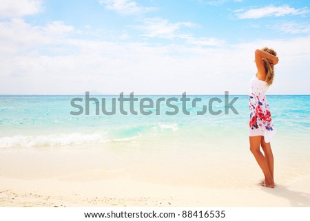 Young woman in dress standing on a beach and looking to a sea - stock photo