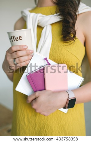 Young woman in dress with notes, smartphone and coffee in hands