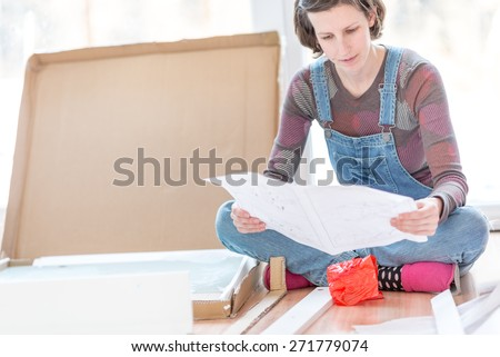 Young woman in dungarees sitting on the floor reading instructions on how to assemble recently delivered flat pack furniture. - stock photo