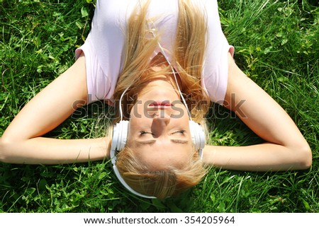 Young woman in earphones on grass - stock photo