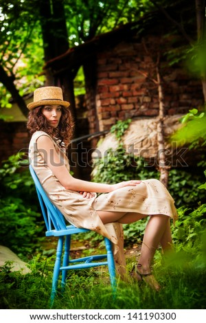 young woman in elegant dress and straw hat sit in garden  summer day - stock photo