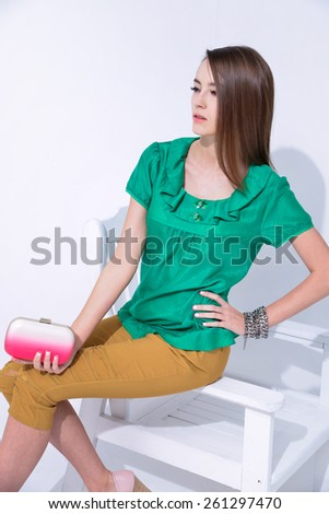 young woman in elegant dress with handbag sitting chair in studio  - stock photo