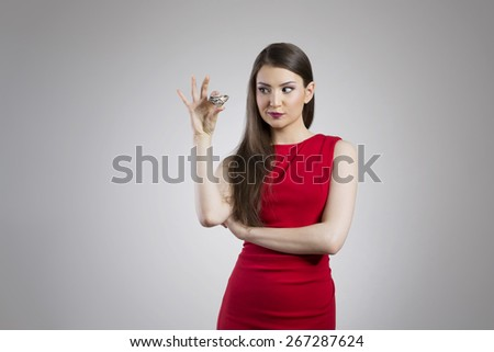 Young woman in elegant red dress holding giant diamond - stock photo
