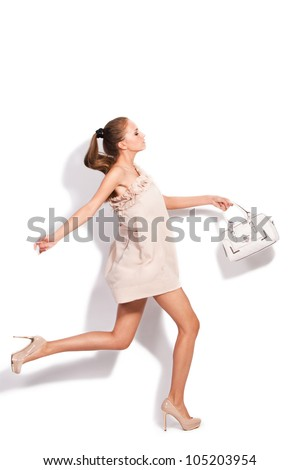 young woman in elegant short dress and high heel shoes run carrying hand-bag, studio white - stock photo