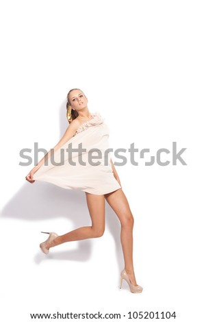young woman in elegant short dress and high heels shoes in motion studio white - stock photo
