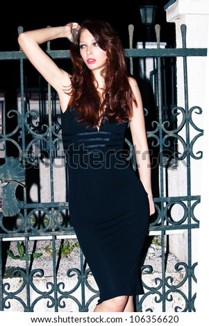 young woman in elegant tight evening dress outdoor shot in front of wrought iron gate - stock photo