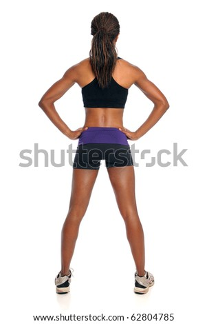 Young woman in exercise outfit standing in back view isolated over white background