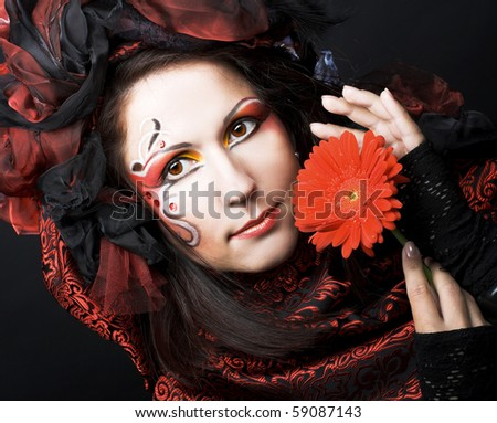Young woman in exotic image with red flower - stock photo