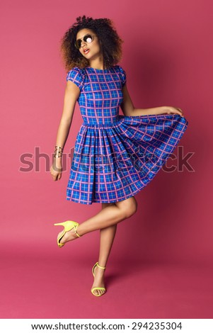 Young woman in fashionable dress and sunglasses on pink background. Afro hairstyle - stock photo