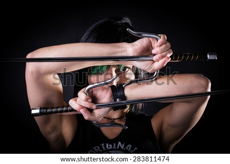 young woman in fighting stance holding a pair of sai: studio portrait on black background - stock photo