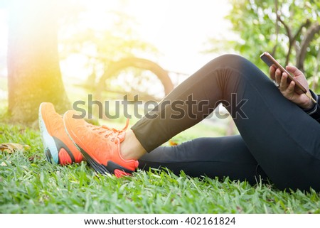 Young woman in fitness clothes is relaxing in outdoor park - stock photo