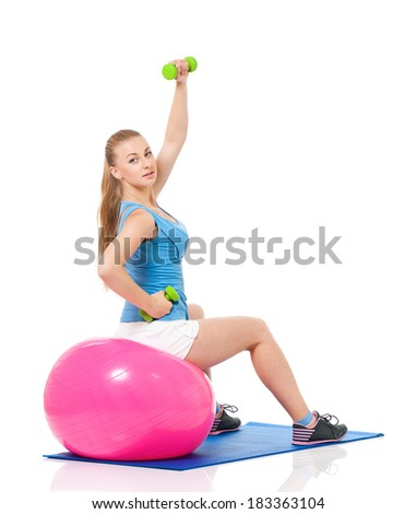 Young woman in fitness wear exercising with fitness-ball and dumbbells, isolated on white background - stock photo