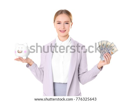 Young woman in formal clothes holding piggy bank and money on white background