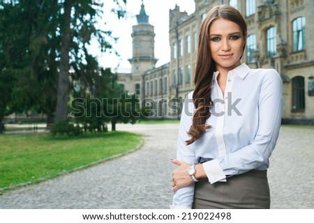 young woman in formal clothes near old university building - stock photo