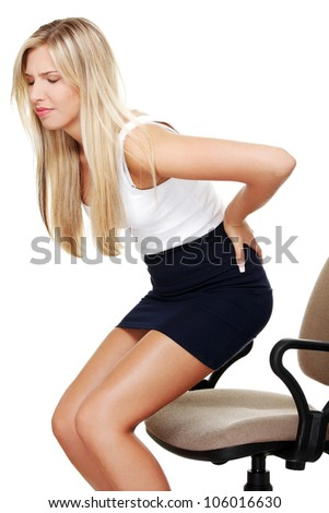 Young woman in formal dress holding hands on waist above her bottom in back pain. Isolated on the white background. - stock photo