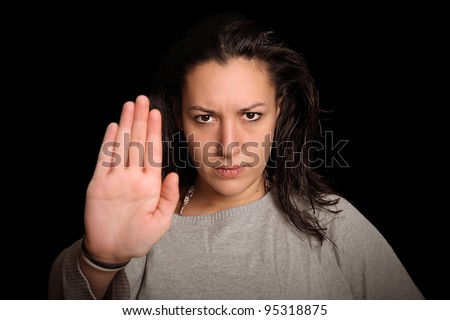 young woman in front of black background holding up her palm to say : STOP !!! - stock photo