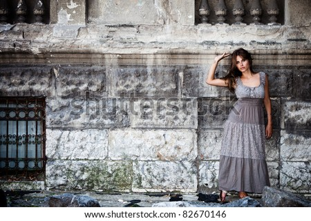 young woman in front of old stone house, outdoor portrait