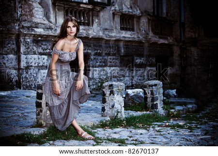 young woman in front of old stone house, outdoor portrait at dusk
