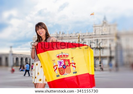 Young woman in front of Palacio de Oriente - the Royal Palace of Madrid, holding a flag with a big smile. - stock photo