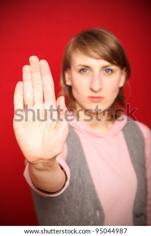 young woman in front of red background defending herself (focus on hand) - stock photo